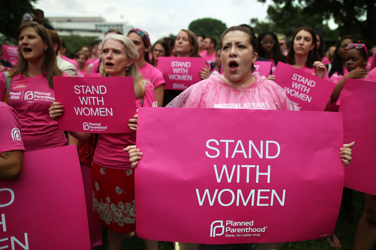Women hold up signs during a women's pro-choice rally on Capitol Hill, July 11, 2013 in Washington, DC.
