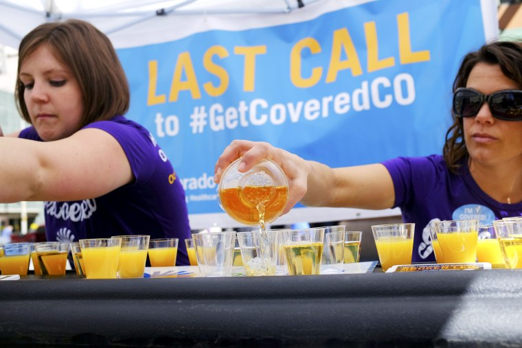 """Workers pour juice as they promote health care coverage during a """"Last Call"""" event in Denver, March 20, 2014."""