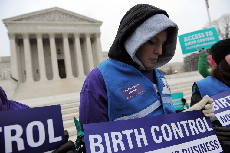 Alena Yarmosky holds a sign outside the Supreme Court of the United States on March 25, 2014 in Washington, DC.