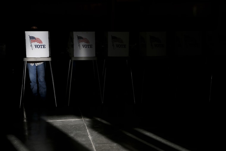 Voting booths are illuminated by sunlight as voters cast their ballots at a polling place in Billings, Mont., Nov. 6, 2012.
