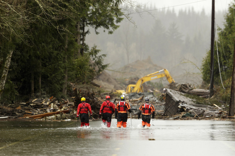 Rescuers walk in floodwaters on Highway 530 as search work continues in the mud and debris from a massive mudslide that struck Oso near Darrington, Washington, March 27, 2014.