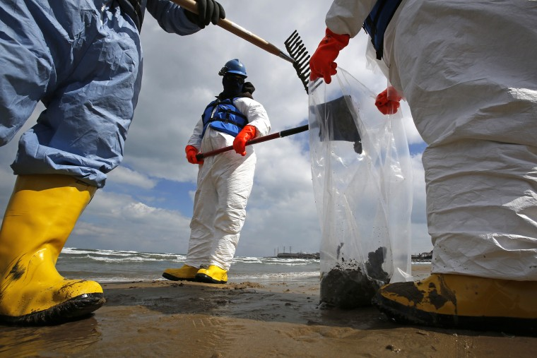 Oil spill response contractors clean up crude oil on a beach after a BP oil spill on Lake Michigan, March 25, 2014, in Whiting, Indiana.