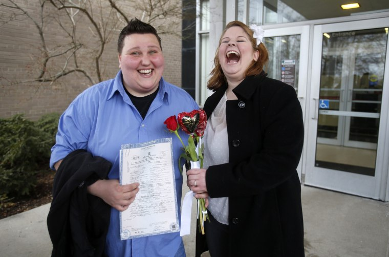 Newly married Sarah Brown (L)  and Dolly Vanfossan hold their marriage license outside after being married at the Oakland County Courthouse in Pontiac, Michigan, March 22, 2014.