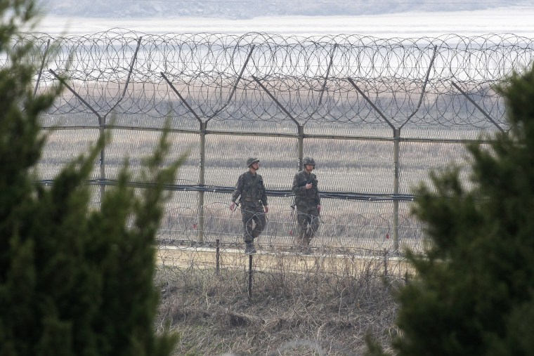 South Korean army soldiers patrol along a barbed-wire fence in Paju, near the border with North Korea, South Korea, March 27, 2014.
