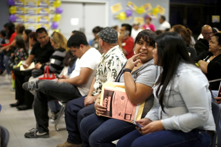 People wait in line at a health insurance enrollment event in Cudahy, Calif. on March 27, 2014.