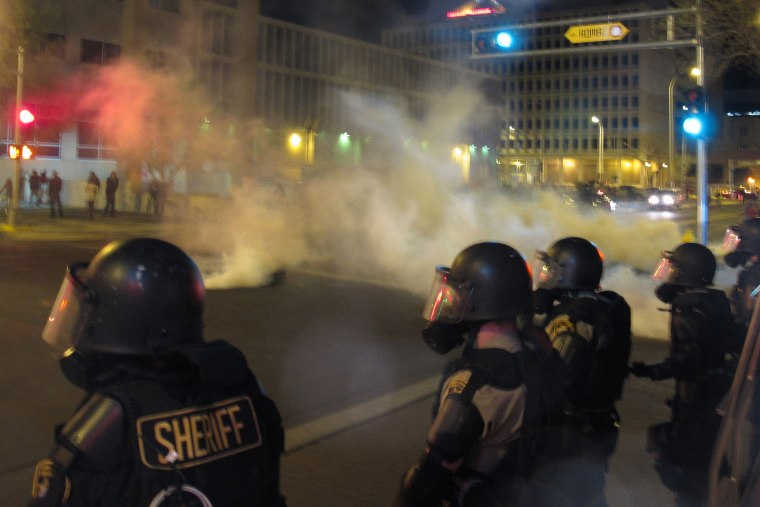 Riot police launch tear gas toward activists in downtown Albuquerque, N.M. following a 10-hour protest around the city, on March 30, 2014.