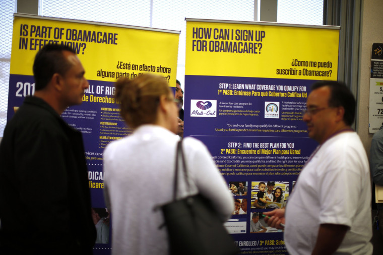 Julian Gomez (R) explains Obamacare to people at a health insurance enrollment event in Commerce, California March 31, 2014.