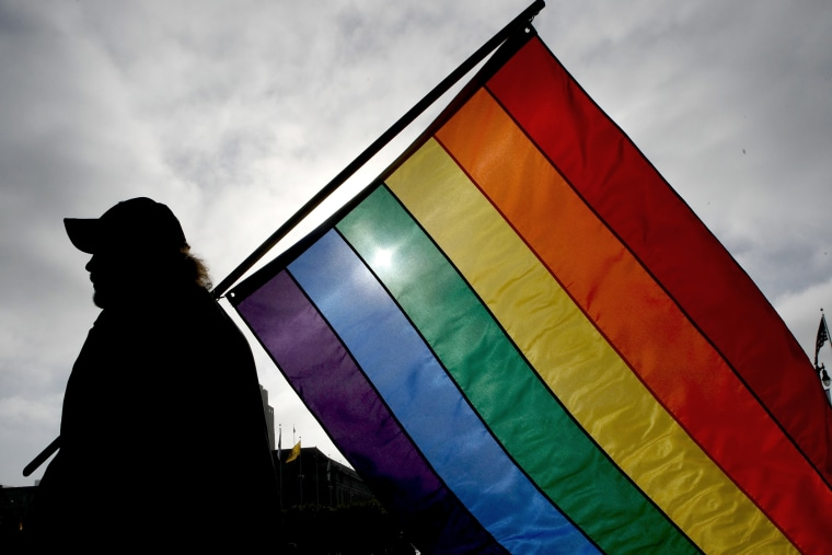 A man holds a gay pride flag.