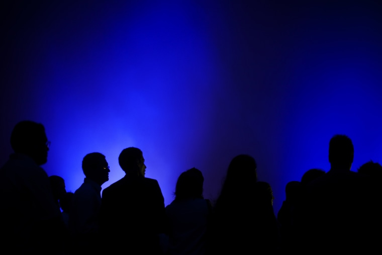 People are silhouetted by blue light as they stand in the fog during a mass commemorating World Autism Awareness Day in Rio de Janeiro, Brazil on April 1, 2011.