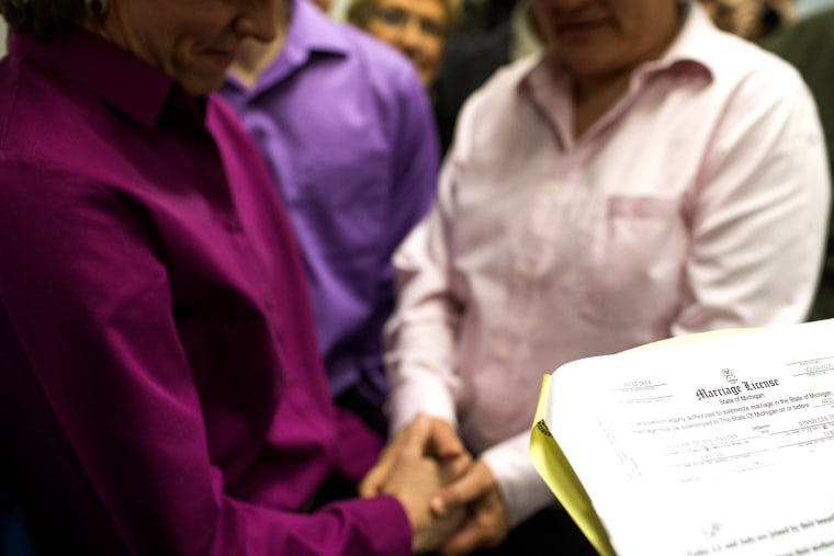 A gay couple holds hands during their marriage ceremony at the Washtenaw County Clerk's Office in Ann Arbor, Mich., on March 22, 2014.