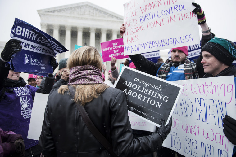 Activists with opposing views about contraceptive health care mix outside the Supreme Court in Washington, DC., Mar. 25, 2014.
