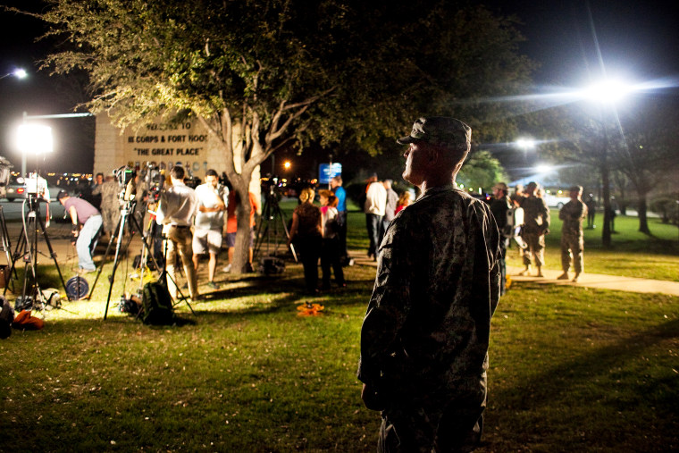 A soldier watches over media as they prepare for a press conference about the shooting at Fort Hood, April 2, 2014.