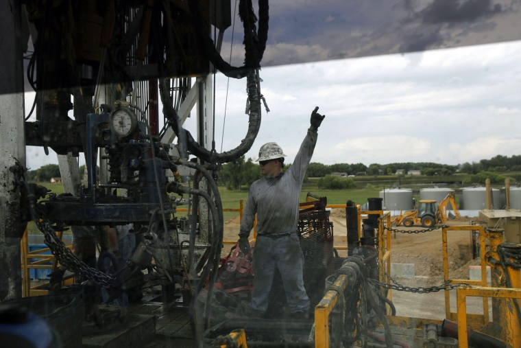 In an Aug. 25, 2009 file photo, a crew member with Anadarko Petroleum Corp., photographed through a car window, works on a drilling platform on a farm near Mead, Colo.