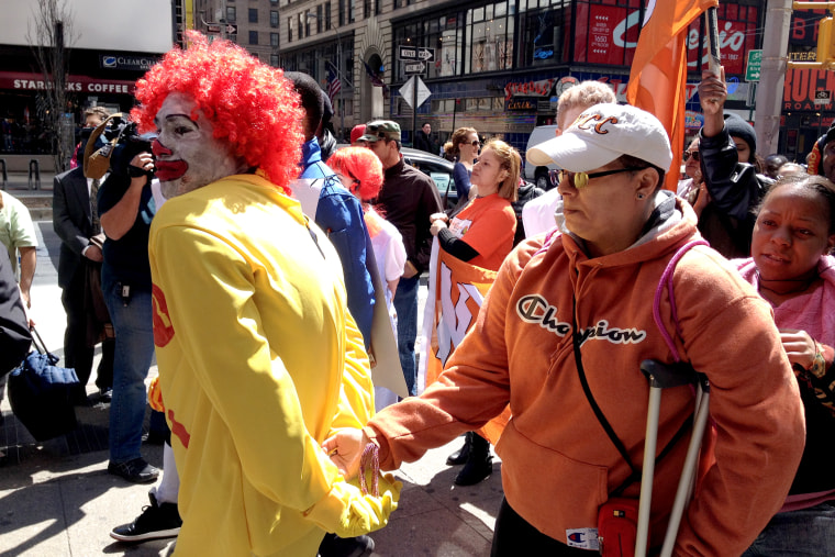 """A protestor dressed as Ronald McDonald is given a mock """"perp walk"""" during a protest against wages in the fast food industry, on April 3, 2014 in New York City."""