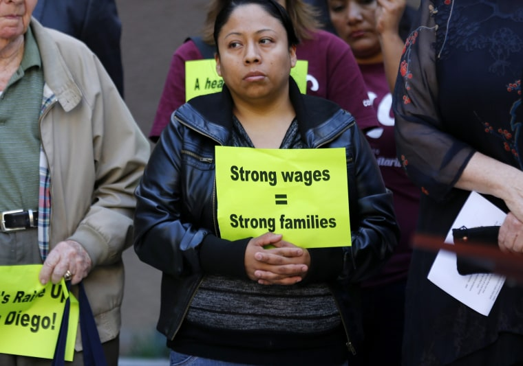 A supporter holds a sign promoting a movement to raise the minimum wage in San Diego, California, March 12, 2014.