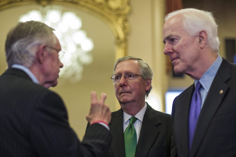 Republican Senate Minority Leader from Kentucky Mitch McConnell chats with Democratic Senate Majority Leader from Nevada Harry Reid in the US Capitol in Washington, D.C., February 12, 2014.