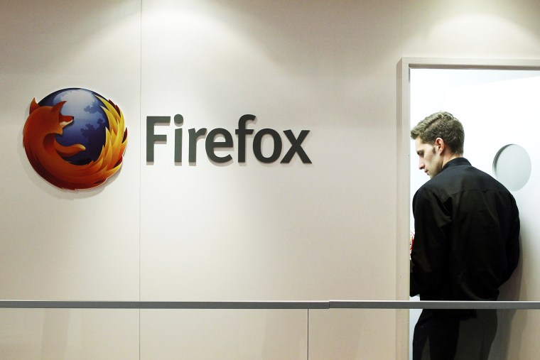 A man is seen next to a Firefox logo at a Mozilla stand during the Mobile World Congress in Barcelona, Feb. 28, 2013.