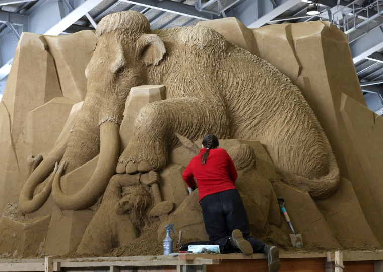 Karen Fralich of Canada finishes a sand sculpture at the Sand Museum in the Tottori Dune on April 3, 2014 in Tottori, Japan.
