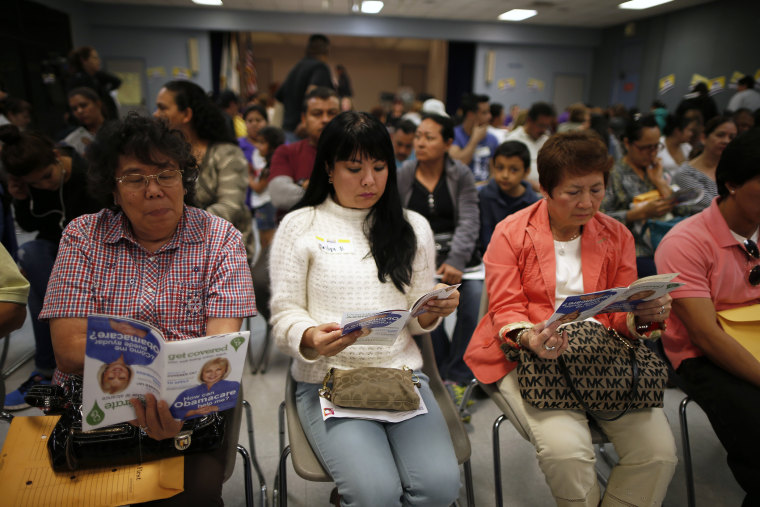 People wait in line at a health insurance enrollment event, March 27, 2014 in Cudahy, Calif.