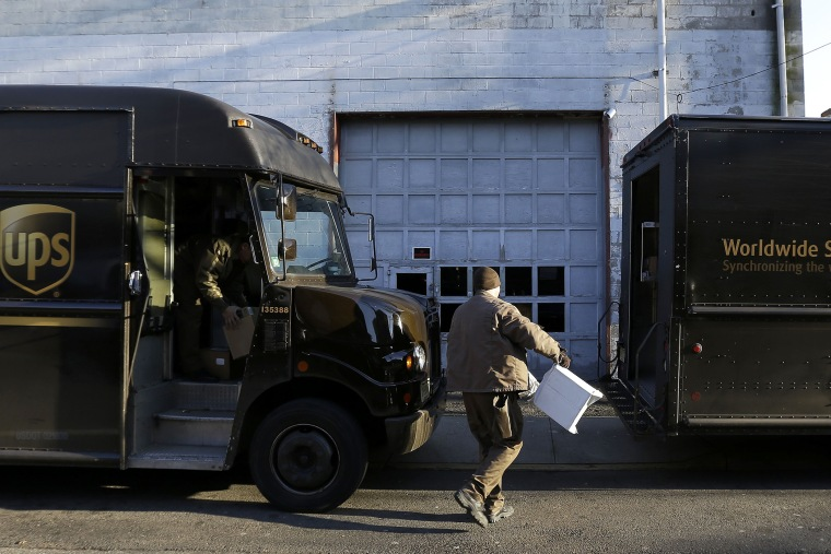 UPS delivery workers move packages from one truck to another, on Dec. 26, 2013, in Newark, N.J.