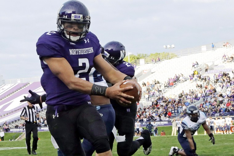 "Northwestern quarterback Kain Colter (2), wears APU for ""All Players United"" on wrist tape as he scores a touchdown, Sept. 21, 2013."