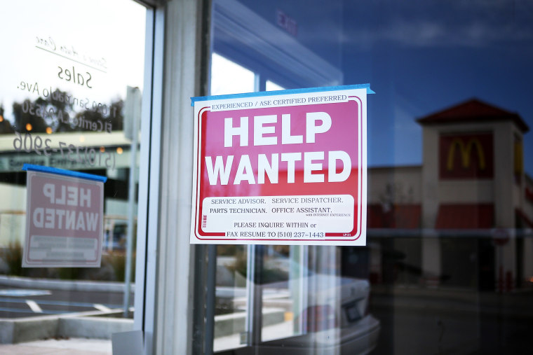 """A \""""Help Wanted\"""" sign is posted in the window of an automotive service shop on March 8, 2013 in El Cerrito, California."""