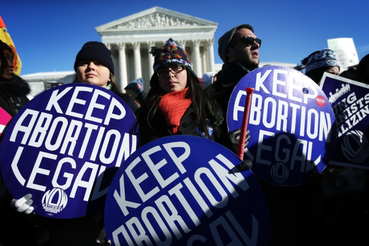 Pro-choice activists hold signs as marchers of the annual March for Life arrive in front of the U.S. Supreme Court on Jan.22, 2014 on Capitol Hill in Washington, DC