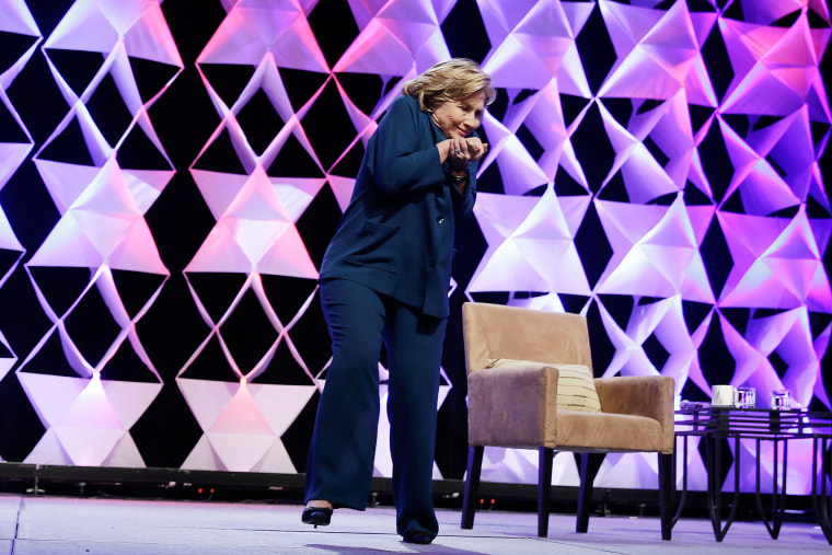 Former Secretary of State Hillary Clinton ducks after a woman threw an object toward her while she was delivering remarks in Las Vegas, April 10, 2014.