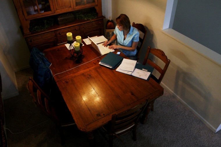 Debbie Jurcak, a mother of three, works on an application for state aid at her apartment in Aurora, Ill. Jurcak, 43, was among many Americans who lost unemployment benefits in late December.
