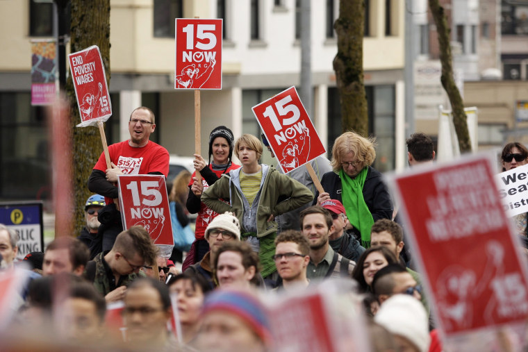 People rally in support of a $15 minimum wage at Seattle Central Community College in Seattle, Washington March 15, 2014.