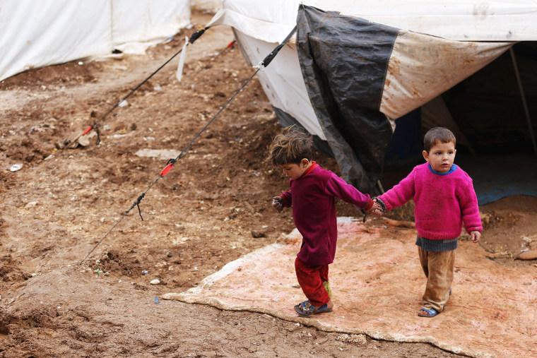 Syrian refugee children walk through mud at the Bab Al-Salam refugee camp in Azaz, near the Syrian-Turkish border, March 14, 2014.