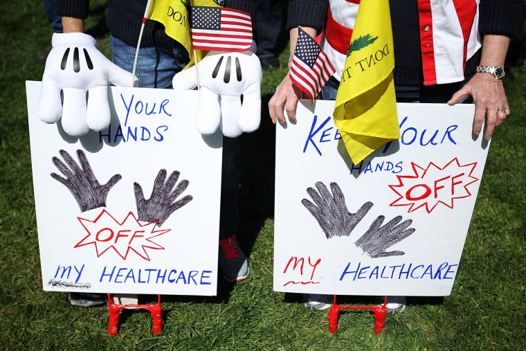 """Tea Party supporters hold signs as they participate during a """"Hands Off My Health Care"""" rally, March 27, 2012 on Capitol Hill in Washington, DC."""