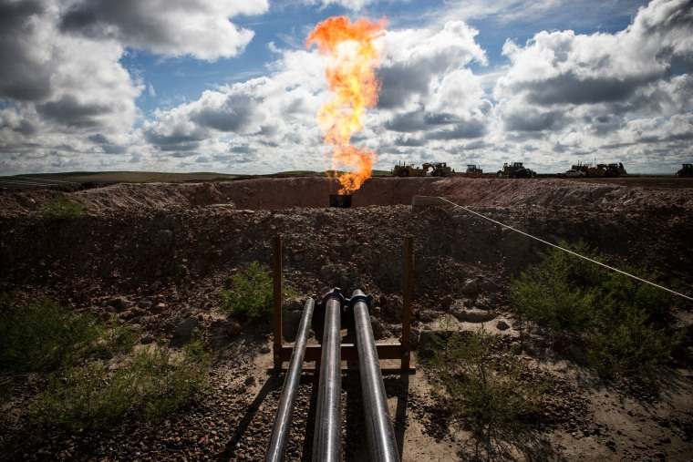 A gas flare is seen at an oil well site on July 26, 2013 outside Williston, N.D.