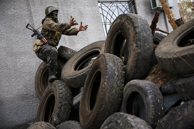 An armed man gestures from a barricade in front of the police headquarters in Slaviansk April 12, 2014.