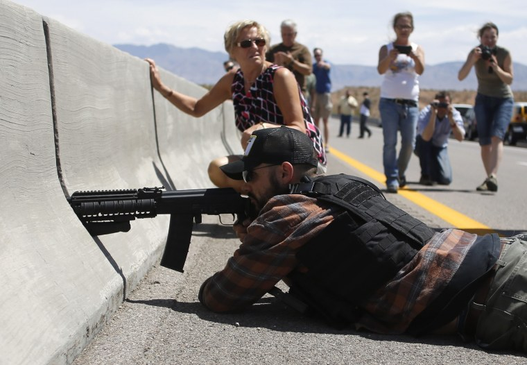 Protester Eric Parker aims his weapon next to the Bureau of Land Management's base camp where seized cattle are being held near Bunkerville, Nevada, April 12, 2014.