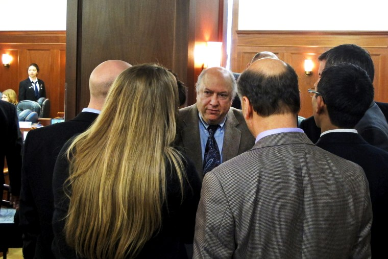 Max Gruenberg, D-Anchorage, huddles with fellow minority Democrats during a break in the floor debate on a minimum wage bill in Juneau, Alaska, April 13, 2014.