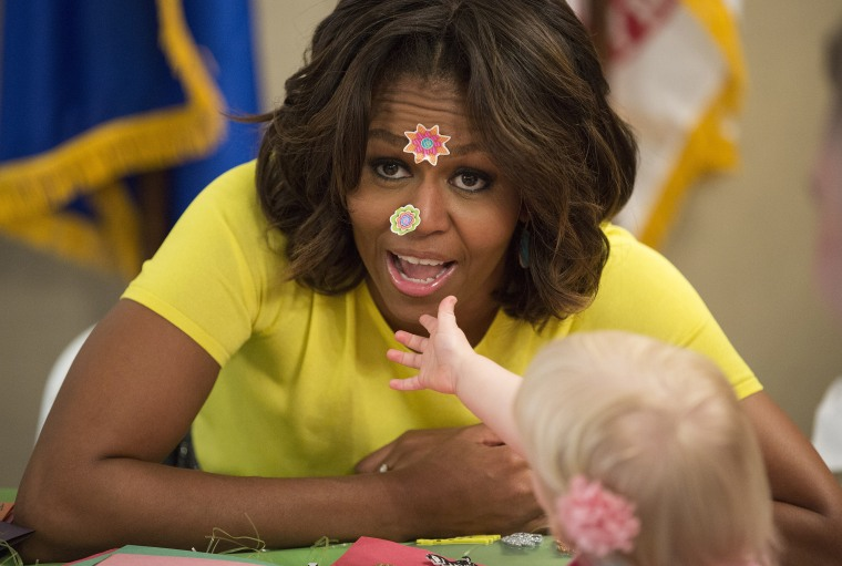 U.S. first lady Obama has stickers put on her face by 20-month-old Oppelt during visit with children at Fisher House at Walter Reed National Military Medical Center in Bethesda