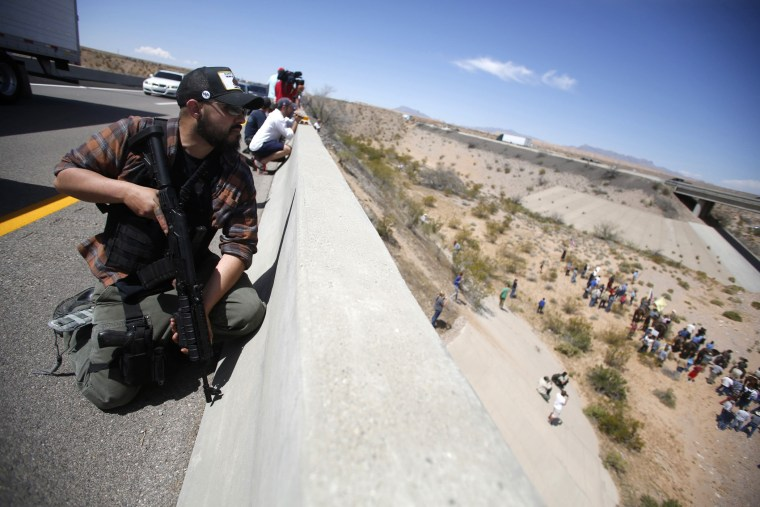 Eric Parker from central Idaho stands watch on a bridge with his weapon as protesters gather by the Bureau of Land Management's base camp, where cattle that were seized from rancher Cliven Bundy are being held, near Bunkerville, Nevada, April 12, 2014.
