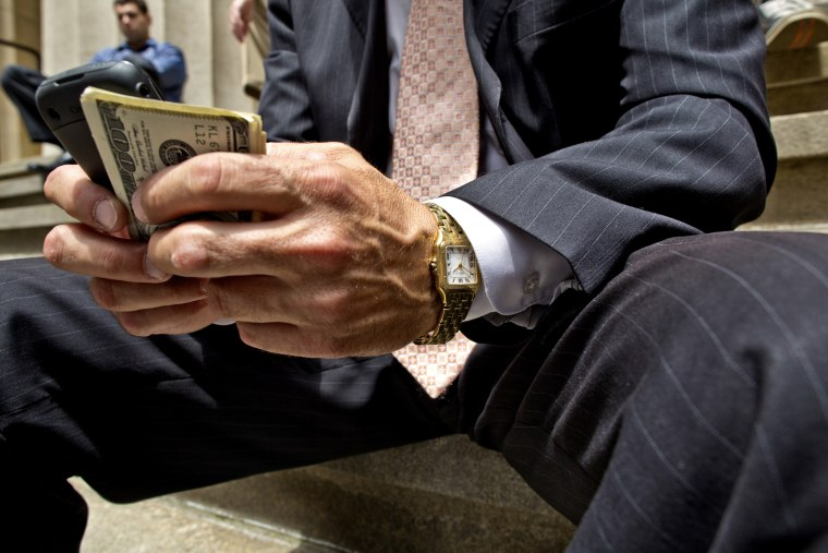 A businessman holding a cellphone and money in downtown Manhattan.