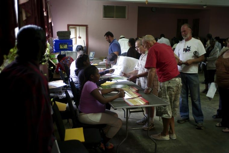 Voters line up to show identification before casting ballots at Deliverance Tabernacle Church of the Nazarene in Miami.