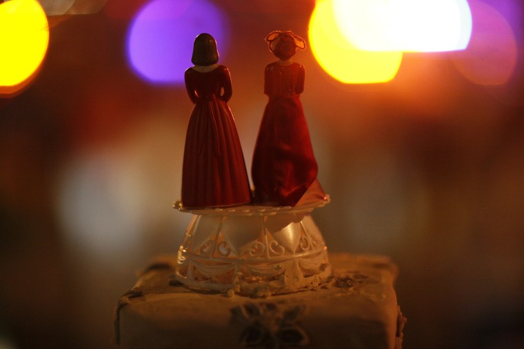 Two bride figurines on top of a cake.