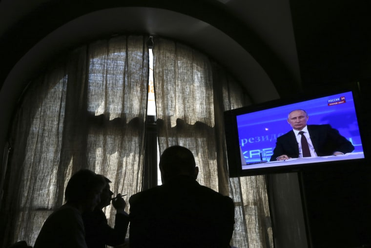 People look at a screen at a media centre during Russian President Vladimir Putin's live broadcast in Moscow on April 17, 2014.