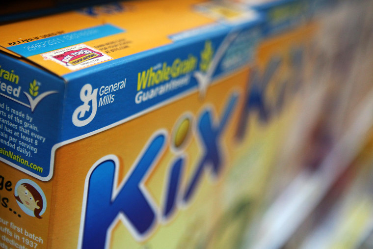 A box of General Mills cereal sits on the shelf.
