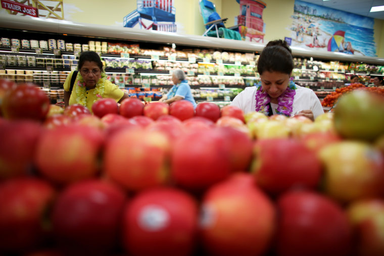 Shoppers look over the produce selection at Trader Joe's in Pinecrest, Fla.