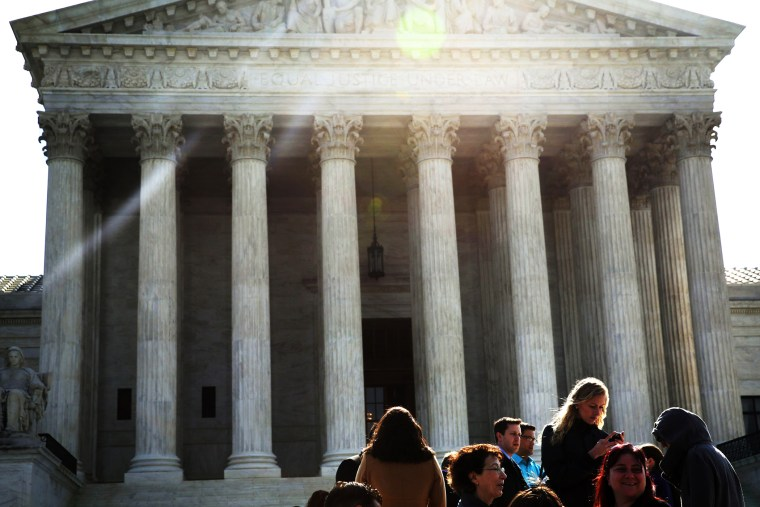 People wait in-line to enter the U.S. Supreme Court to hear oral arguments April 22, 2014 in Washington, DC.