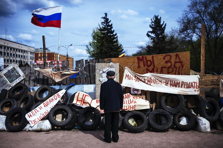 An elderly man stands next a barricade near the secret service building in the eastern Ukrainian city of Lugansk, April 22, 2014.