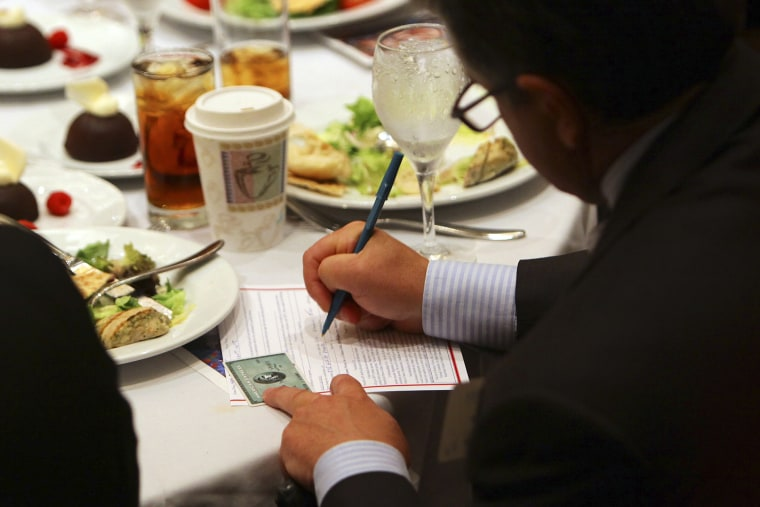 An attendee makes an additional donation during a fundraiser in Atlanta on Sept. 19, 2012.