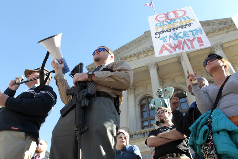 Michael Rugh (2nd-L) holds a AR-15 rifle as he participates along with David Mace (L) and Luchie Wooten (R), during the Guns Across America pro-gun rally at the State Capitol in Atlanta, Georgia, Jan. 19, 2013