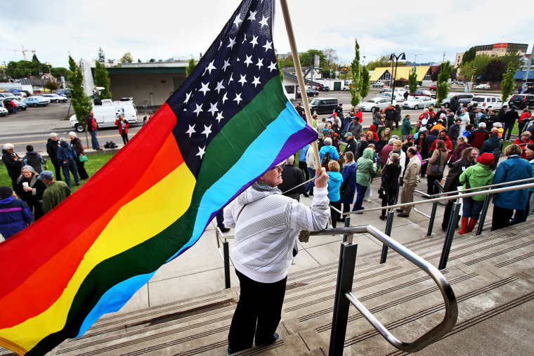 Teresa Shelley waves a rainbow-colored American flag on the steps of The Wayne L. Morse United States Courthouse Tuesday, April 22, 2014 in Eugene, Ore.