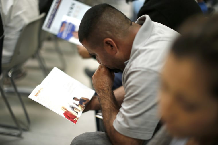 People read pamphlets as they wait in line at a health insurance enrollment event in Cudahy, California on March 27, 2014.